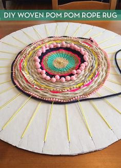 turn a piece of cardboard, some strands of rope and a few pom poms into a beautiful bohemian rug.