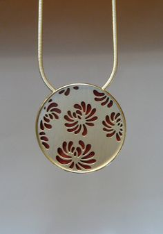Large Round Chrysanthemum Necklace with Red Copper.  Sterling silver and patinated copper necklace with pierced chrysanthemum design on a sterling snake chain. The design is inspired by Japanese katagami which were used to silkscreen kimono fabric. In this necklace there is a hand made bezel holding the copper and the pierced silver pieces on the back to protect the skin from the copper.  All pieces with patinated copper will vary due to the unpredictable results of the patination process.