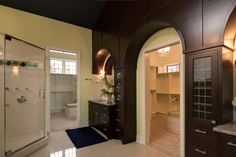 Stained cabinetry with arched opening. Granite countertops. Tile and carpet flooring. Semi-frameless walk-in shower with tile walls and deco band. Painted MDF closet shelving.