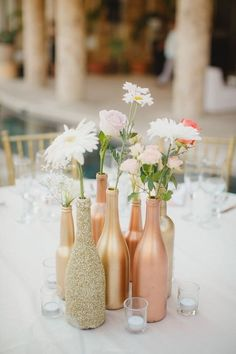 Once the rosé is gone, don't be quick to rid of those wine bottles until you've seen this DIY wedding idea. Start by soaking some empty wine bottles until the labels come off. After they're clean and dry, spray paint each bottle with at least two coats of metallic paint in metallic shades like rose gold. You can also coat one in glitter to create a cluster of unique wedding centerpieces. #quickweddingplanning #fastweddingplanning