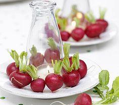 Kleid aus Radieschen  Einen Teelichthalter aus Glas, einen kleinen Teller und ein paar Radieschen: Mehr braucht man für die Natur-Tischdeko nicht! Das Teelicht inklusive Glashalter kommt auf den Teller. Rundherum legen Sie die Radieschen. Ihr leuchtendes Rot wirkt appetitanregend und frisch. Und am Ende wird die Deko einfach aufgegessen!