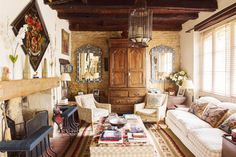 This living room is arranged for comfort and conversation. A tall cabinet, typical of this part of France, is is flanked by mother-of-pearl mirrors bought from India, and a huge lantern brought back from Morocco. Exposed walls hark back to the building's history.