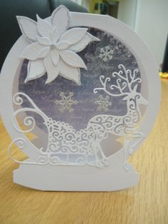 Snow globe card using Tattered Lace reindeer and sleigh dies, Poinsettia flower, sparkly snowflakes.