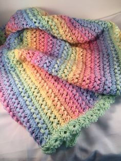 Made to Order Baby Afghan This crochet baby blanket is bright and colorful and sure to be eye catching. I crocheted this baby afghan with a high quality acrylic yarn in a rainbow of pastel colors. This baby afghan is crocheted in the hairpin lace pattern. Hairpin lace is an old stitch crocheted with a loom to make strips of loops. Those loops are weaved together to make the afghan. It was then trimmed with a mint green broomstick lace border. This afghan is loose and airy which makes it…