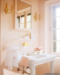 in Martha Stewart's guesthouse in Maine: Additional pinks are worked into the decorative scheme in the bathroom with a few embroidered towels and some soaps.