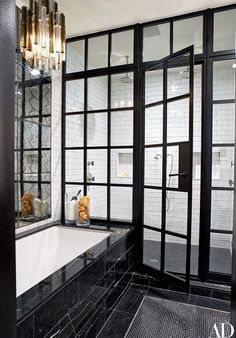 The master bath's shower fittings and tub are by Kallista, and the tiles on the tub surround, walls, and floor—as well as the python-patterned mirrored tile—are by Ann Sacks.
