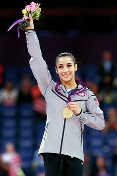 Team USA's Aly Raisman waves from the podium after winning the gold medal in the women's gymnastics floor exercise event final at the London Olympics.