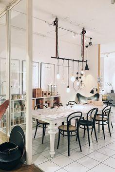 como-decorar-un-salon-comedor-mesa-blanca-sillas-negras-baldosas-pared-de-vidrio-bombillas-colgantes Interior Minimalista, Patio, Dining, Kitchen, House, Home Decor, Rustic Style, Black Chairs, White Tables
