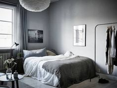 A bed in a calm, cocoon-like Swedish space in greys. Stadshem.
