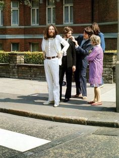 august 8, 1969. john, ringo, paul and george lining up in a candid shot from ian mcmillan's iconic  cover photoshoot for abbey road. nice of paul to help with ringo's collar.