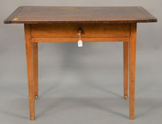 """Federal tavern table with rectangular top over drawer set on square tapered legs, wood wheels in two legs, circa 1790.  ht. 28 in.; top: 27 1/2"""" x 38""""  Estimate: $300 - $500"""