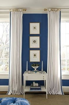 Bedroom by Kelley Proxmire with white curtains with blue trim and royal blue walls: