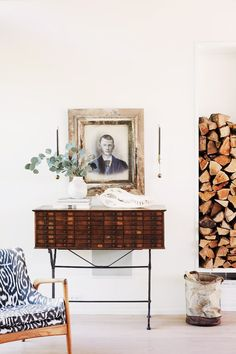 Wood storage beside console table and antique art