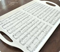 Old plastic tray, primer, white spray paint, sheet music cut in strips, Modge Podge on tray, strips, 2 layers Modge Podge (dry between all coats).  LOVE this!