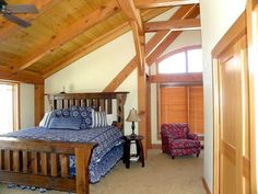 Post and beam framing using Douglas Fir timbers are found in the master bedroom in this Adirondack styled vacation ski home.