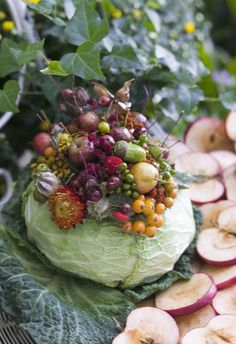 A DIY fall table centerpiece that features an arrangement of flowers and vegetables placed in a cabbage vase.