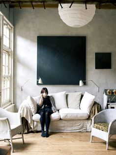 Contast:Modern  Black painting, white paper lantern, Granny style easy wicker and slouchy couch.