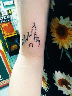 Pequeño tatuaje de la silueta del castillo de Disney en el bícep derecho.