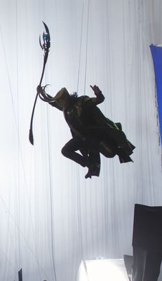 Tom Hiddleston as Loki in The Avengers on the wire harness for stunts with the glow stick of doom