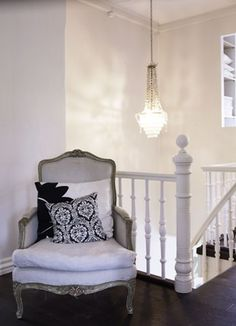 elongated chandelier in staircase foyer + french chair