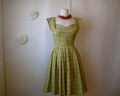 vintage 1950s dress in a pretty olive-y muted chartreuse color. lovely polished cotton with a darker olive butterfly or moth embroidery all over. sweetheart bust with a fitted waist and a pleated skirt that is oh so full. rear metal zipper and hook and eye.