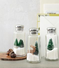 """Here's one Yuletide idea that's definitely worth its salt: Turn under-a-dollar shakers into mini winter wonderlands by nesting toy evergreens and deer atop iodized """"drifts."""""""