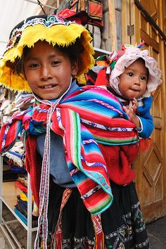 Young girl in traditional dress and baby sister, Pisac Sunday market, Peru-The bread from Pisac is the best ever! I love that town.