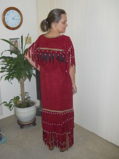 This is the back side of the red dress ...It's fully fringed at sleeves, across front and back and bottom has double layers of fringe all fringe across top is adorned with beads and feathers and bottom fringe is adorned in beads only. This one ismade of a faux suede but can very easily be done in buckskin.