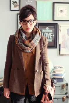 She looks a little sullen but her outfit is cool. Love the blazer an scarf.