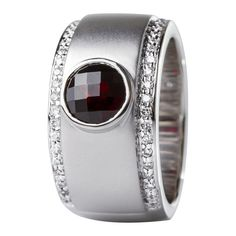 Sortija en oro blanco de 18 kilates con granate y diamantes incoloros. 18K white gold ring with garnet and diamonds.