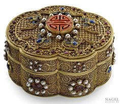 A gold lidded box, China, Qianlong period or later, engraved four character Qianlong to base. decorated with wire decoration of foliate design, its lid with red coral shou-character surrounded by bat motifs, box and lid lavishly set with cabochon sapphire, ruby as well pearls, 388,8 grams, 18-21 kt.
