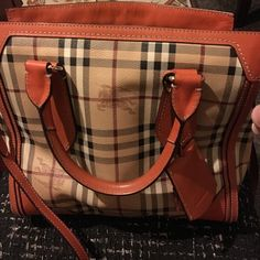 Burberry handbag A Burberry orange handbag with tan colors. It is 11 w x 11 h x 9 d . The interior is tan with a back zipper pocket and 2 more pockets on reverse side . It is a decent size handbag which was gently used and has a dust cover. Burberry Bags Totes