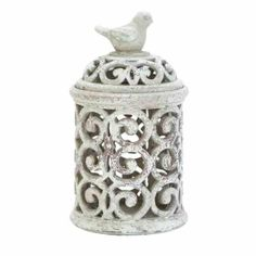 """Shabby Chic Large Sculpted Distressed Ceramic Covered Jar with Bird on Lid  This covered jar features sculpted ceramic in a trellis motif and light distressing on the sides of the jar. The jar of this lid features a sculpted bird perched as the handle of the lid. You can add a large pillar candle to this covered jar to add a light accent to your space. This covered jar is the perfect shabby chic addition to any modern space!  Overall Dimensions of This Covered Jar: 12"""" H x 8"""" Dia"""