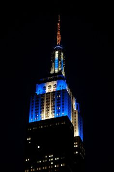 December 6, 2015: In celebration of Chanukah, the Empire State Building illuminates New York City with white and blue lights and a flickering candle antenna.