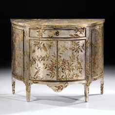Cabinet with floral and bird design on an antiqued silverleaf background, two doors, one drawer and antiqued brass hardware. Hand painted and hand finished. 40 in. W x 32.5 in. H x 16 in. D