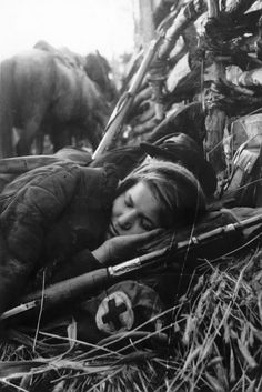 A nurse is getting some sleep on the frontline. You can see the field repairs on her rifle.