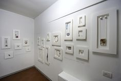 white frames out from wall - wonder about white eye hooks and tiny ridged blocks affixed to wood backing to hang necklaces and earrings