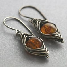 These pretty little earrings are coin-shaped amber wrapped in sterling silver wire using a herringbone weave. They dangle from handformed sterling silver ear wires. I oxidized and polished the sterling silver to give it an antiqued patina. These earrings are fairly lightweight. They measure 1 1/2 inches (4cm) in length from the tops of the ear wires.