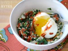 Fiber filled brown jasmine rice, chopped spinach, a creamy soft boiled egg, and a splash of sriracha make a quick, healthy, and delicious breakfast.