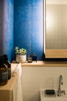 Lacquered wallpapers bring a vibrancy of colour to the bathroom.