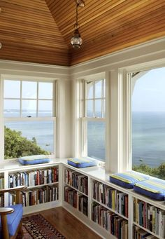 wow bookshelves / library with big white undressed windows overlooking the sea - who needs curtains? ;)