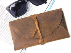 This gorgeous new leather pouch is one of our most versatile leather accessories!  You can use this wrap pouch to hold sunglasses, pens/pencils, tobacco or even use it as a wallet or purse that will hold your smart phone. #gift #adventure #giftguide #vintage #leather #travel