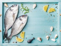 Pic: Fresh raw sea bream fish decorated with lemon slices herbs and shells in blue tray copy space