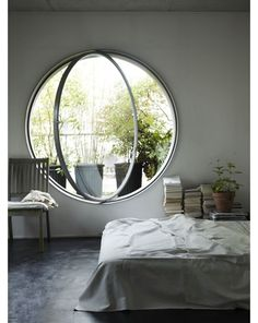 A round window is traditionally referred to as an oculus. They are traditionally placed high up on building facades or at the pinnacle of domes. Installing one in a bedroom is a charming touch. Go large scale to keep if from feeling too much like a porthole.