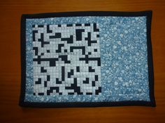 Quilted Mug rug. crossword in black, white and blue