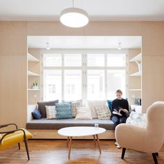 Birch-plywood cabinets completely surround a set of windows in this renovated 1930s home in Prague, creating a cosy lounge space framed by space-saving solutions. Read the full story on dezeen.com/interiors #interiors #prague #spacesaving Photograph by Alexandra Timpau.