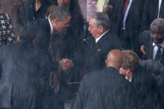President Barack Obama (left) shakes hands with Cuban President Raul Castro during the official memorial service for former South African President Nelson Mandela at FNB Stadium December 10, 2013 in Johannesburg, South Africa.