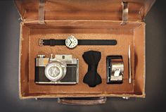 The Electric Watch in Stainless Steel and black silicone by Newgate Watches : Flat lay featuring a vintage suitcase with a vintage camera, bow tie/dicky bow calendar and parker pen.