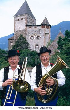 Musicians in traditional costumes standing in front of the Forte Castle, Italy - Stock Image
