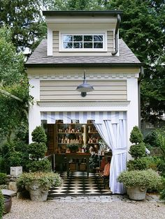 Perfect garden shed with topiaries, workroom upstairs, farmhouse pendant, gravel, black and white checked floor, dentil moulding and striped curtain and awning material